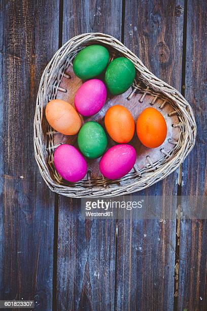 Green and pink Easter eggs in wicker basket