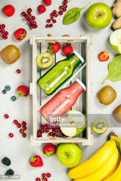 Green and red fresh juices or smoothies with fruit, greens, vegetables on grey background, top view, selective focus. Detox, dieting, clean eating, vegetarian, vegan, fitness, healthy lifestyle concept