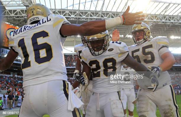 J Green and TaQuon Marshall of the Georgia Tech Yellow Jackets celebrates a touchdown during a game against the Miami Hurricanes at Sun Life Stadium...
