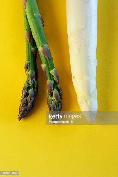 Green and white asparagus on yellow background, close-up