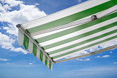 green and white striped awning against blue sky
