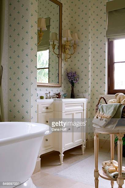 Green and white wallpapered bathroom with painted wooden furniture