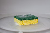 A green and yellow sponge covered in soap suds sits inside of a microwave
