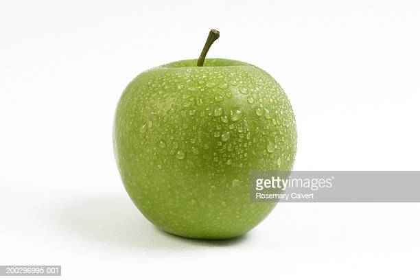 Green apple covered in water drops, close-up