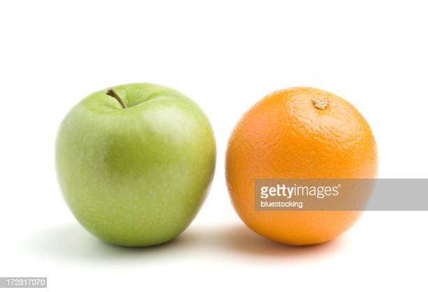 A green apple next to an orange, isolated on white