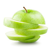 Photograph of green sliced apple over white background. Apple is brightly illuminated with drop shadow