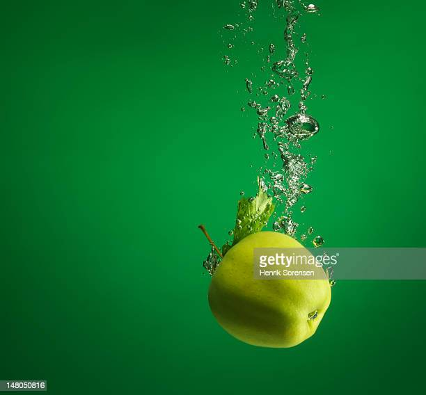 green apple splashed into water