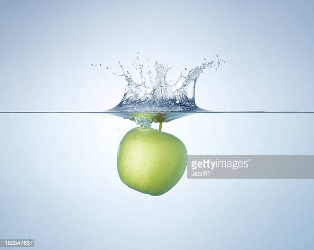 Green apple splashing into water