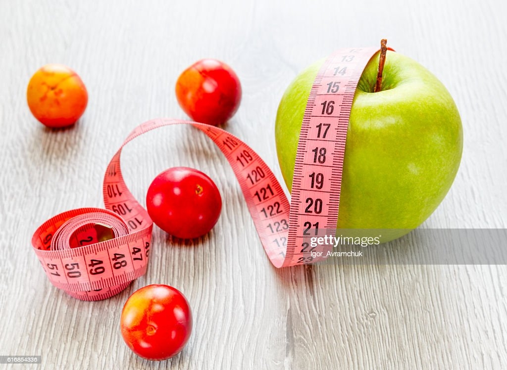 Green apple with a meter and plum : Stock Photo