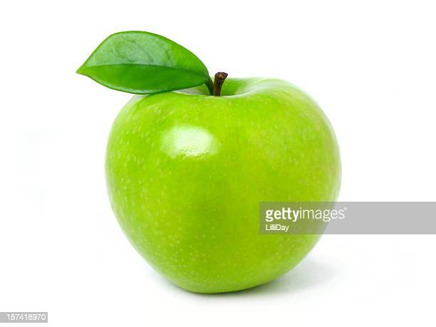 Green apple with leaf on a white backdrop