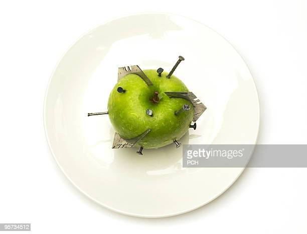 Green apple with razor blades and nails stuck in