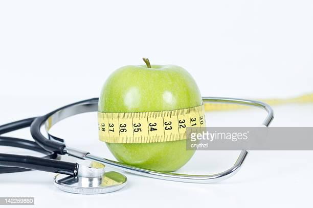 Mela verde e nastro di misurazione avvolto con Stetoscopio