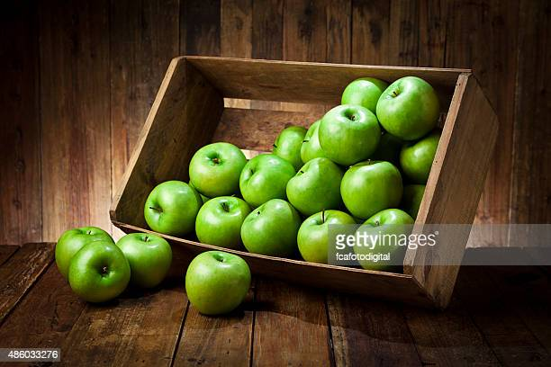 Green apples in a crate on rustic wood table