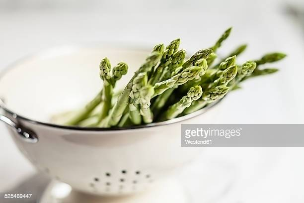 Green asparagus in colander