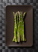 Green asparagus on a brown plate