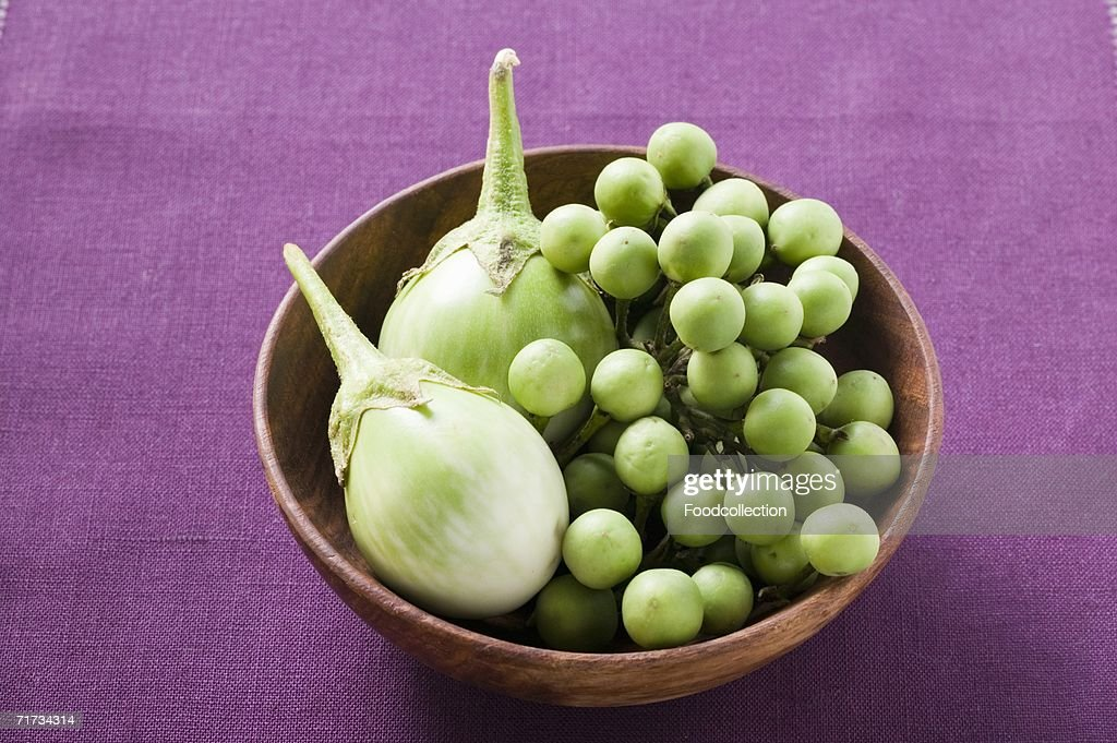 Green baby aubergines in wooden bowl : Stock Photo