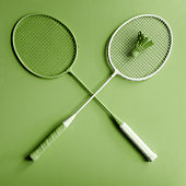 Green badminton racket on green background. Creative fashion sports series. Greenery Pantone color of the year 2017