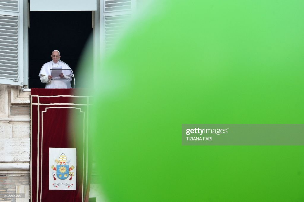 A green balloon flies as Pope Francis addresses the crowd from the window of the apostolic palace overlooking St Peter's square during the Sunday Angelus prayer, on February 7, 2016 in Vatican. / AFP / TIZIANA FABI