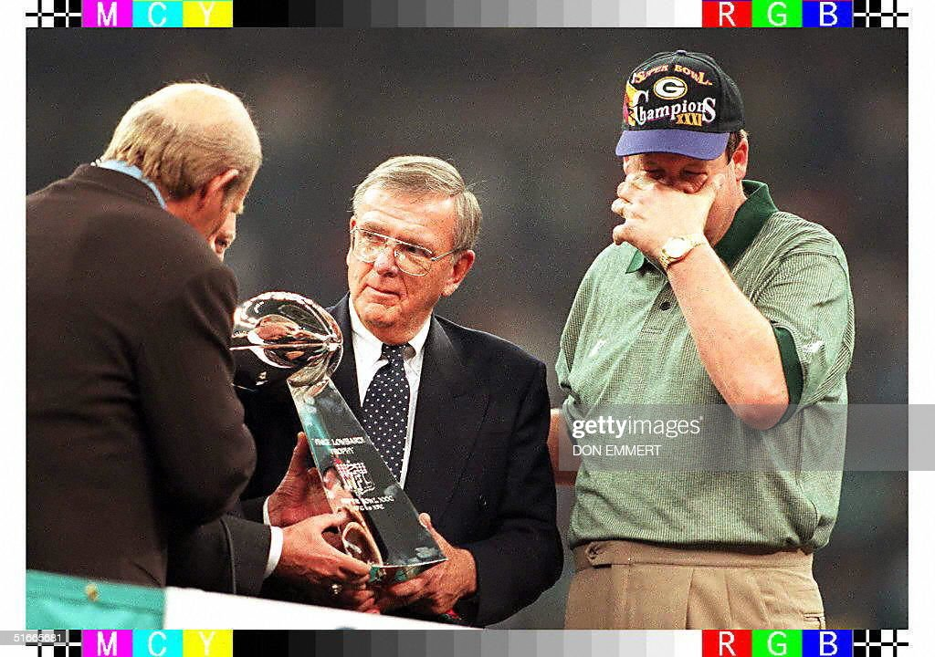 Green Bay Packers coach Mike Holmgren wipes his eyes as Packers General Manager Ron Wolf receives the Vince Lombardi Trophy at the Louisiana...