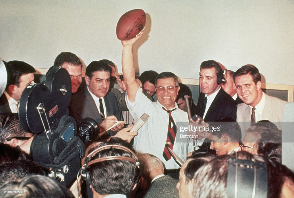 Green Bay Packers coach Vince Lombardi raises a football in victory surrounded by reporters covering the first Super Bowl in 1967