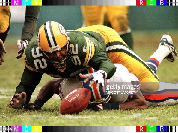 Green Bay Packers defensive end Reggie White jumps over Denver Broncos tight end Shannon Sharpe to recover a fumble by Bronco's quarterback Bill...