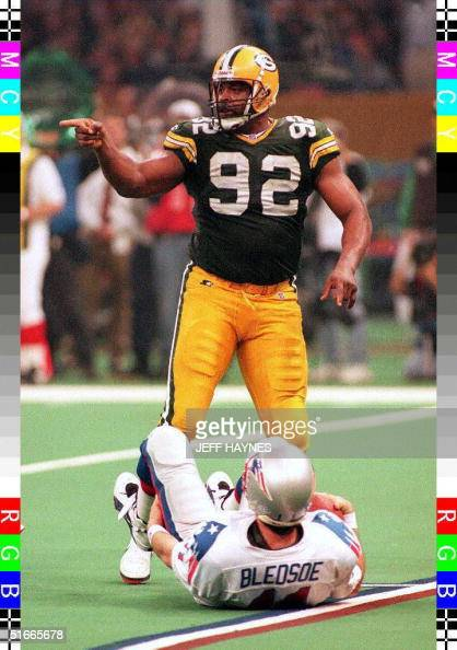 Green Bay Packers defensive tackle Reggie White points to teammates after sacking New England Patriots quarterback Drew Bledsoe 26 January during the...