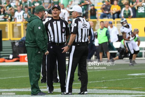 Green Bay Packers head coach Mike McCarthy talks with side judge Gary Cavaletto and referee Bill Vinovich during a football game between the Green...