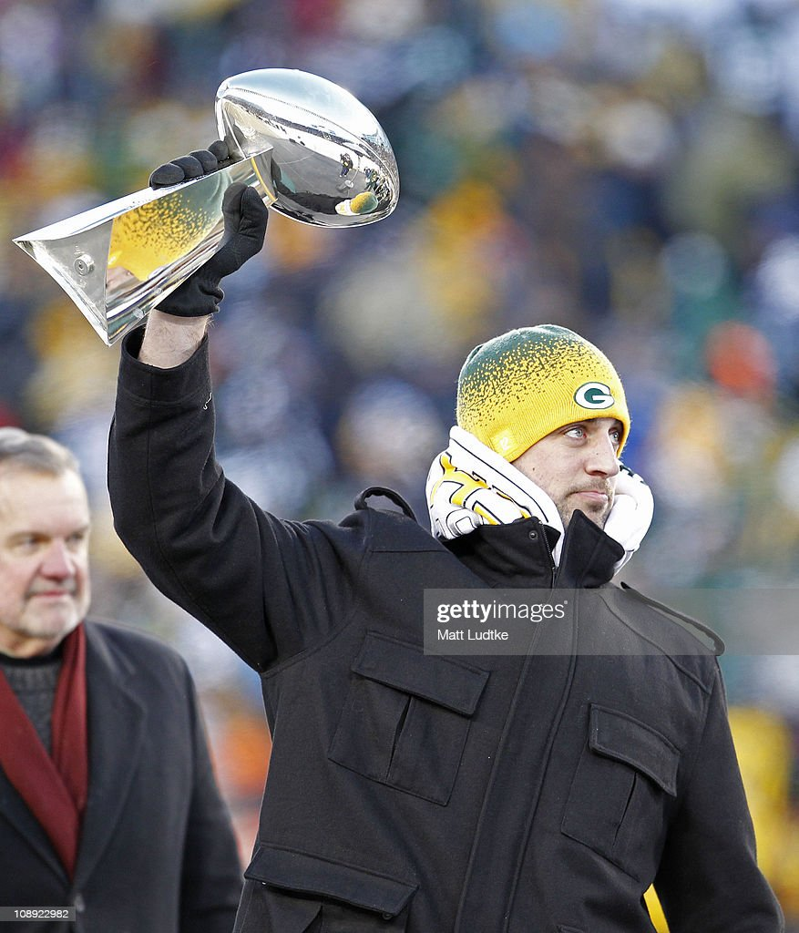 Green Bay Packers quarterback <a gi-track='captionPersonalityLinkClicked' href=/galleries/search?phrase=Aaron+Rodgers+-+Football-Spieler+-+Quarterback&family=editorial&specificpeople=215257 ng-click='$event.stopPropagation()'>Aaron Rodgers</a> hoists the Lombardi Trophy during the Packers victory ceremony at Lambeau Field on February 8, 2011 in Green Bay, Wisconsin.