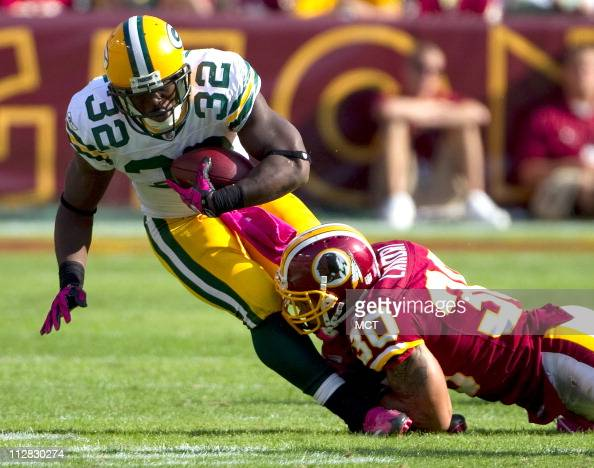 Green Bay Packers running back Brandon Jackson is tackled by Washington Redskins safety LaRon Landry during the 4th quarter at FedEx Field in...