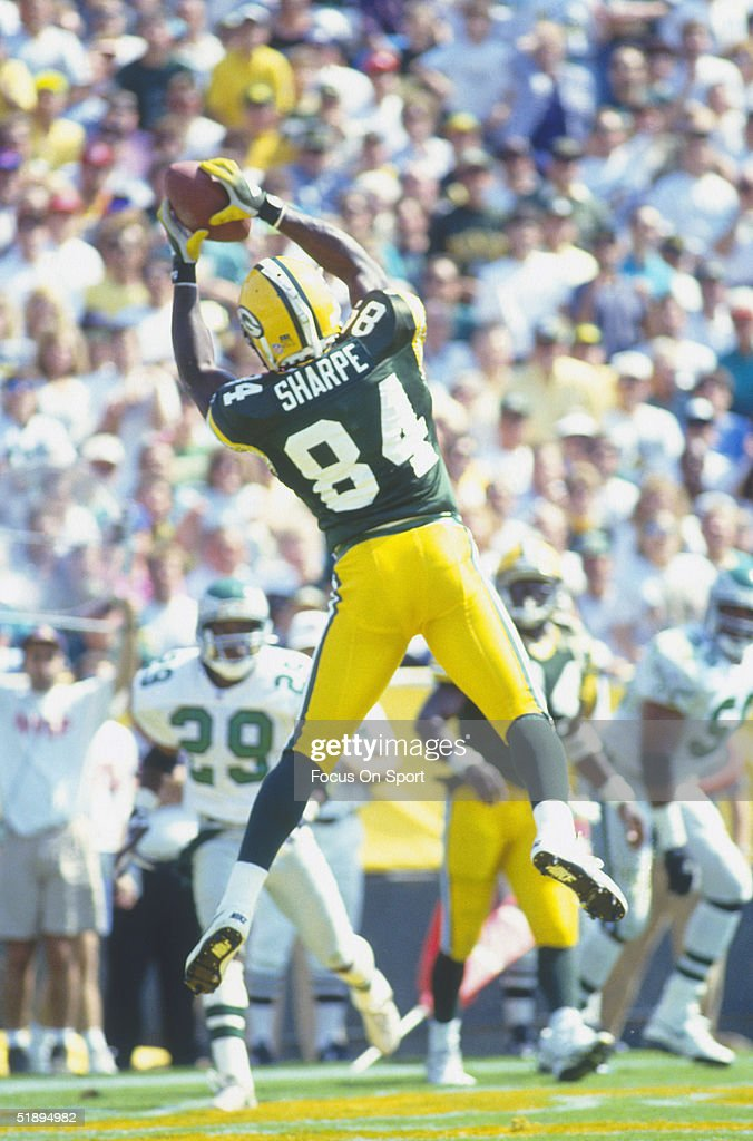 Green Bay Packers' Sterling Sharpe #84 jumps and catches the ball against the Philadelphia Eagles during a game at Lambeau Field in 1993 in Green Bay, Wisconsin.