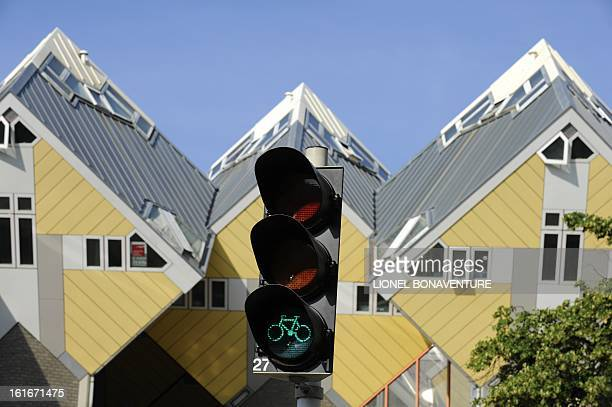A green bicycle appears on a traffic light next to cubic houses on July 2 2010 in center Rotterdam on the eve of the start of the 97th edition of the...