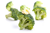 Green broccoli with butter as a garnish isolated on white background