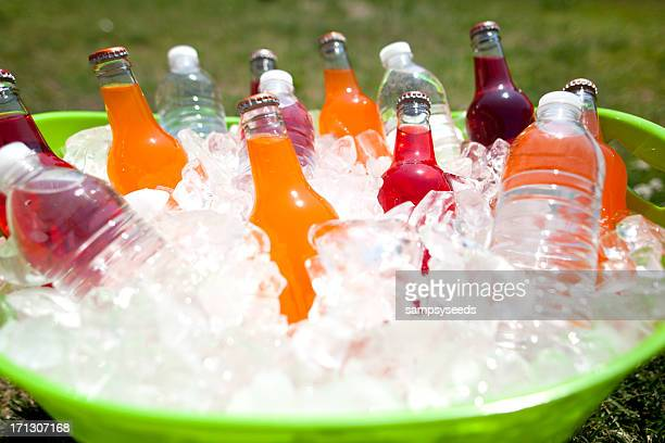 Green bucket filled with water and soda bottles over ice