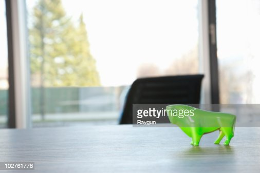 Green bull standing on conference table : Stock Photo
