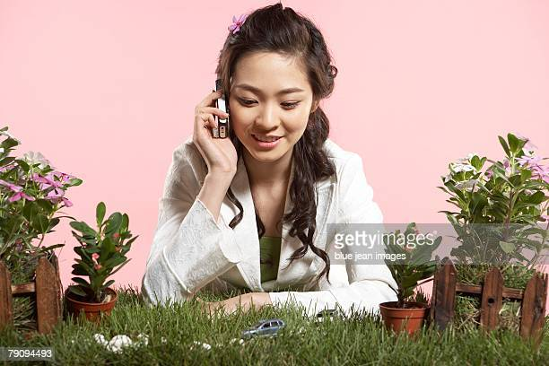 Green' businesswoman making a phone call at a grassy desk.