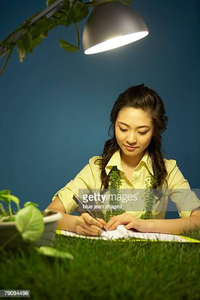 Green' businesswoman working at a grassy desk.