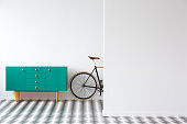 Green cabinet next to bike against white wall in flat interior with checkerboard floor and copy space