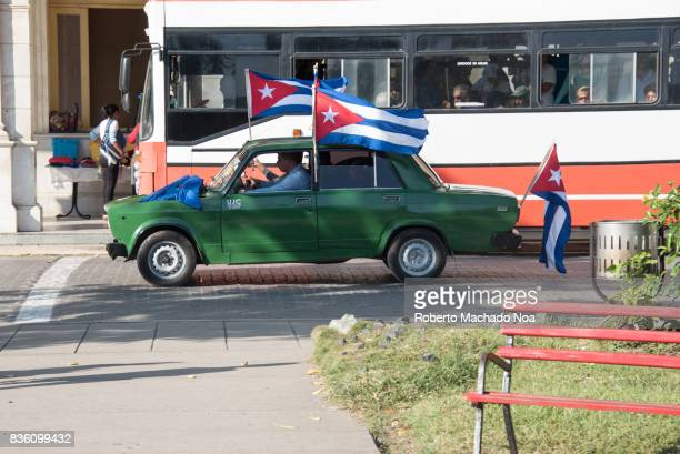 Green car with three National Flags and white pink bus driving side by side beside a public park Celebrating the 'Student Day' in the Leoncio Vidal...