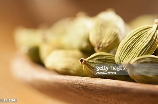 Green cardamom seeds in small wooden bowls