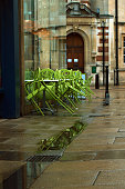 Green chairs relectingin pavement on street of Cambridge