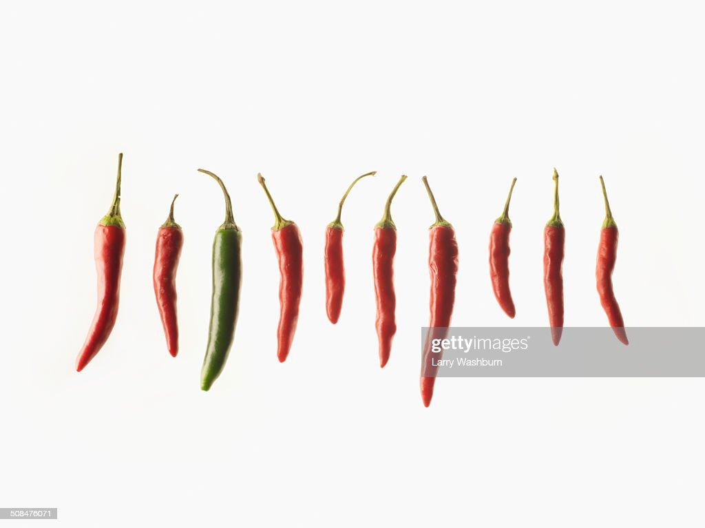 Green chili amidst red chilies over white background