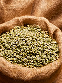 Green coffee beans in sack, close-up