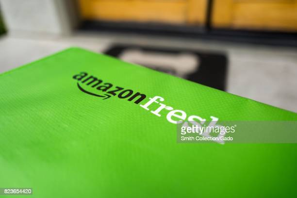 Green cold pack tote for Amazon Fresh grocery delivery service with Amazon logo and text listing groceries which may be ordered using the service on...