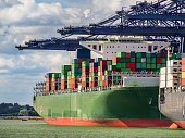 Huge green contaner ship under loading operation with blue gantry cranes in the port of Felixtowe
