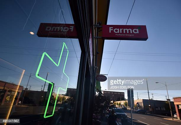 A green cross shines in a window at Farma a marijuana dispensary in Portland Oregon on October 4 2015 As of October 1 2015 a limited amount of...
