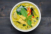 green curry with chicken (Kang Keaw Wan Gai) on wooden background top view, Thai local food