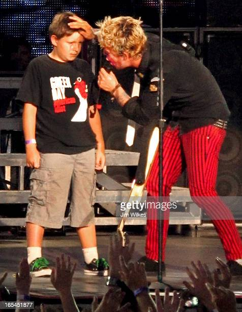 DAY 1 08/19/10 Green Day guitarist/singer Billie Joe Armstrong prepares to lay a 'healing' on Sawyer a 9yearold boy he brought onstage during the...