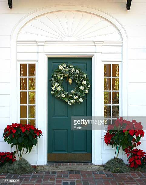 Green door to a white house with a Christmas wreath on it