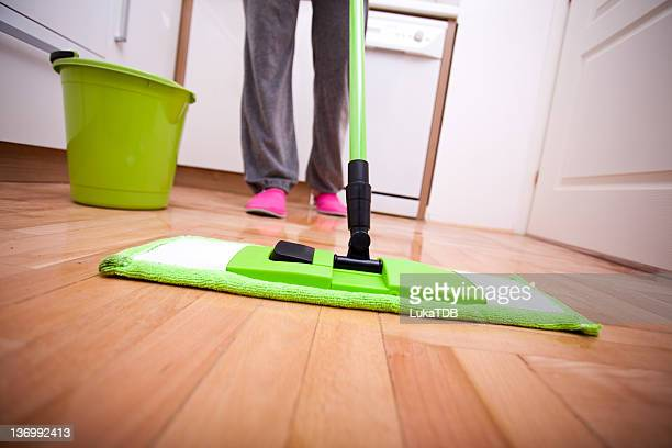Green dust mop and bucket on wood flooring