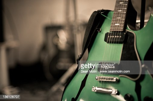 Green electric guitar with blurry background